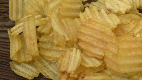 Rippled potato chips on a wooden background Footage