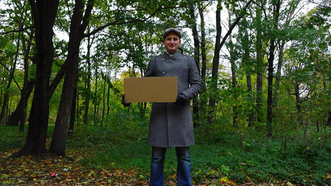 Man pose with empty cardboard sign (copy space) at dim green autumn park Footage