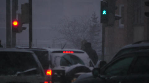 crossroad of city with winter snow blizzard. driving Cars, walking people, red a Filmmaterial