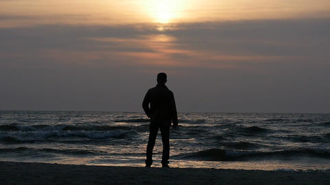 fixed static silhouette of man at evening sea shore before sunset Footage