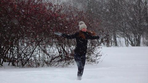 Happy girl dance under snow, large snowflakes fly around, slow motion Footage