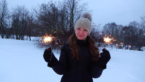 Woman hold sparklers in hands and look to camera, dusk winter park Footage