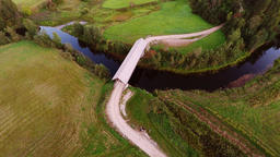 Aerial footage of wooden bridge over river. Flying around Filmmaterial