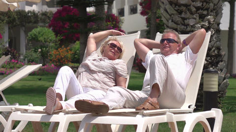 Video of senior couple relaxing on the sunbeds in real slow motion Live Action