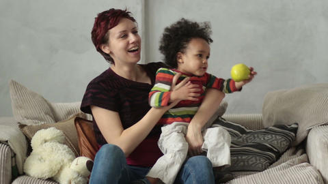 Mother playing with mixed race toddler son on sofa Footage