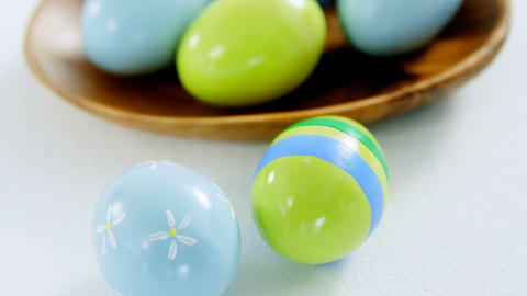 Colorful Easter eggs in bowl with two painted Easter eggs Footage