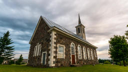 Old catholic church with massive clouds. Epic sunset. Timelapse Footage