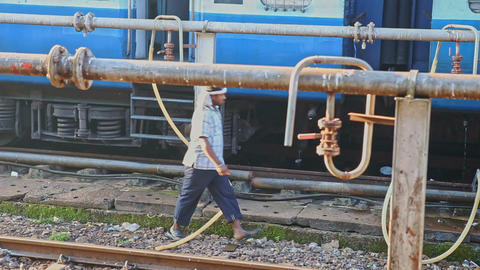 Worker Disconnects Water Pipes from Train System on Station Footage