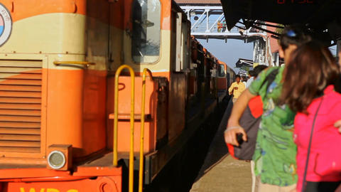 Orange Passenger Train Arrives to Crowded Platform Footage