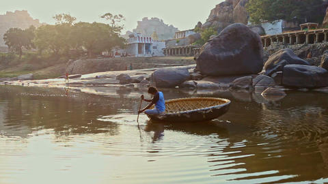 Indian Man Sails in Round Boat along River by Old Town on Bank Footage