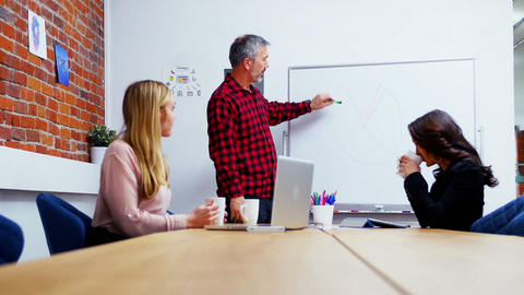 Business executives discussing over whiteboard during meeting Live Action