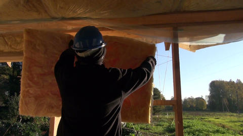 Builder wearing blue helmet insulating farm house frame Live Action
