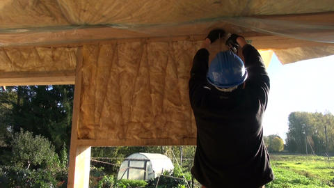 Builder wearing blue helmet insulating house wall Live Action