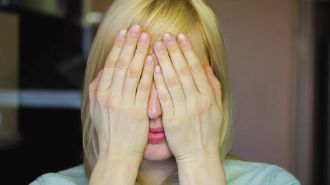 Blonde with different eyes looks at the camera and Remove her hands, heterochrom Footage