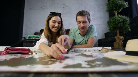 Hipster couple placing pins on scratch travel map Live Action
