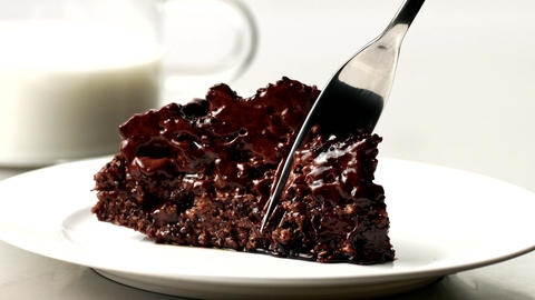Slice of chocolate cake in white dish and a fork took a piece of it off Footage