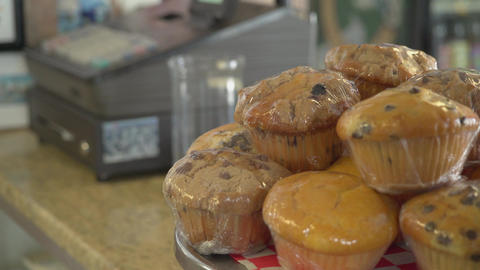 Muffins ready for purchase near cash register Live Action