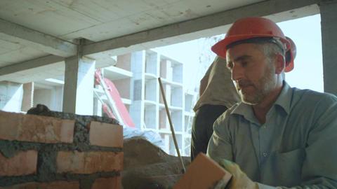 Stone Mason in Red Helmet Lays Bricks on Inner Wall Footage