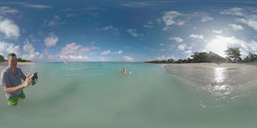 360 VR Family with child bathing in ocean and taking video of vacation on Maurit Archivo