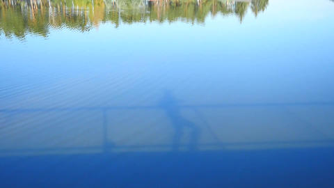 Shadows play in water. Silhouette of tall man running at steel handrail on the b Footage