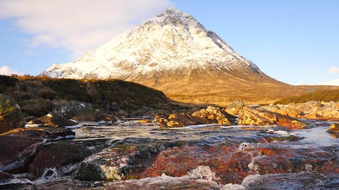 Sunny winter morning at frozen river Coupall at delta to river Etive. Snowy cone Archivo