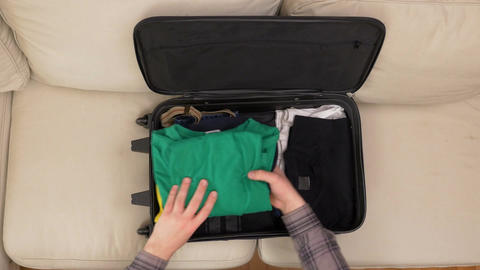 Top view of male hands packing clothes and preparing suitcase for travel Footage
