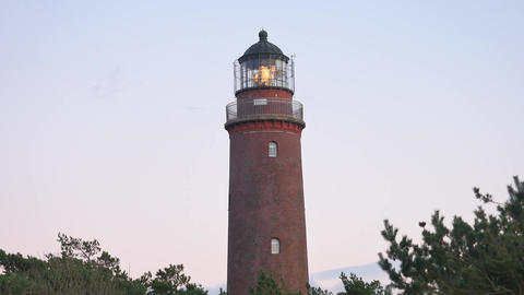 Shinning old lighthouse above pine forest before sunset. Tower illuminated with  영상물