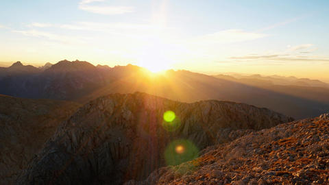 Timelapse of sunset over mountain peaks. Sun goes down over sharp peaks of Alps. Footage