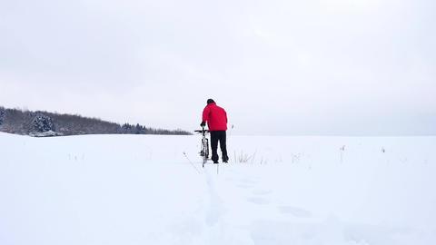 Man with mountain bike on snowy filed. Biker is pushing bike in deep snow. Cloud Archivo