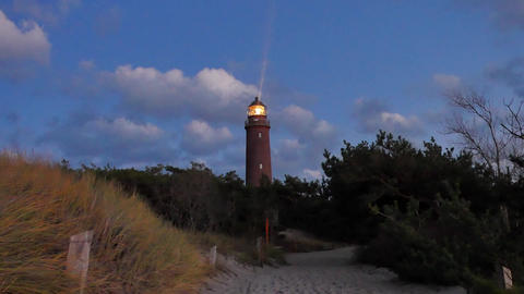Shinning old lighthouse above pine forest before sunset. Tower illuminated with  Archivo