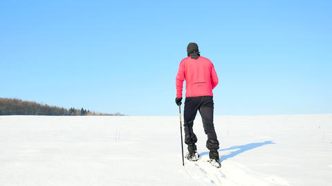 Winter tourist with snowshoes walk in snowy drift. Hiker in pink sports jacket a Archivo