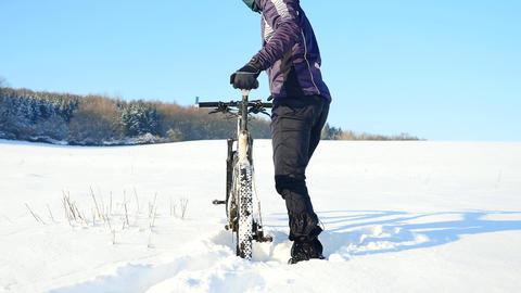Biker pushing mountain bike on snow drift. Freeze sunny winter weather. Biker is Archivo