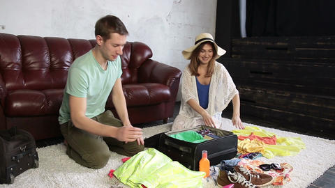 Excited couple packing traveler case for vacation Live Action