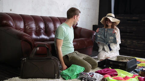 Cheerful couple packing travel bag at home Live Action