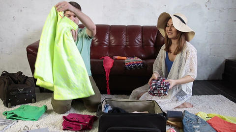 Delighted couple preparing for vacation at home Live Action