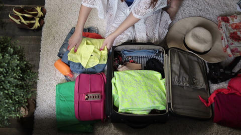 Female hands packing clothes into travel bag Live Action