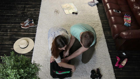 Couple trying to close overfilled suitcase Live Action
