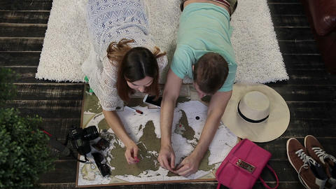 Young family marking places to visit on travel map Archivo