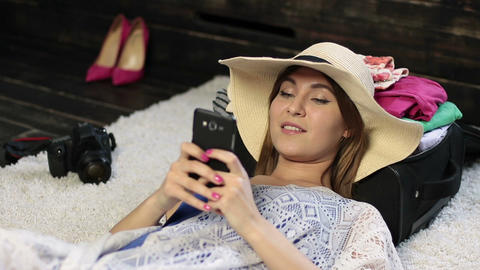 Woman lying on floor text messaging on cell phone Footage