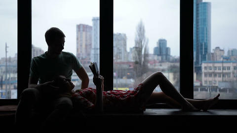 Silhouette of couple reading book on windowsill