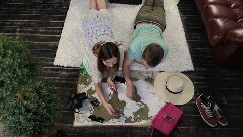 Couple scratching visitited countries on world map Footage