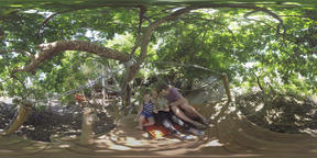 360 VR Family with pad relaxing on wooden deck in the wood at riverbank Archivo