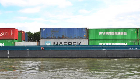 Large barge with shipping containers passing on the canal between the city of Am Footage