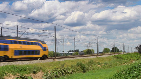 An intercity doubledecker train of the Dutch Railways (NS) is passing at high sp Footage