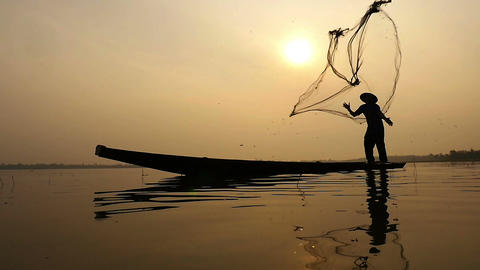Slow motion of Silhouette of traditional fishermen throwing net fishing in the l Footage