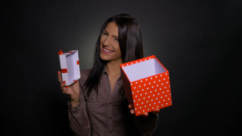 Smiling woman opens surprise gift box and offers it to birthday celebrated Footage