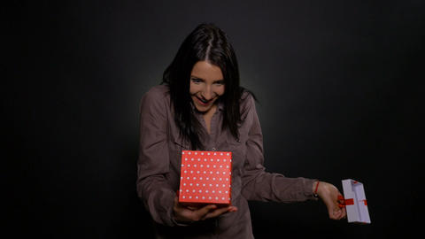 Excited and surprised young woman opens her present gift box on her birthday Footage