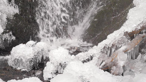 Icicles bellow waterfall. Snowy and icy stones and boulders with drops of fallen Footage