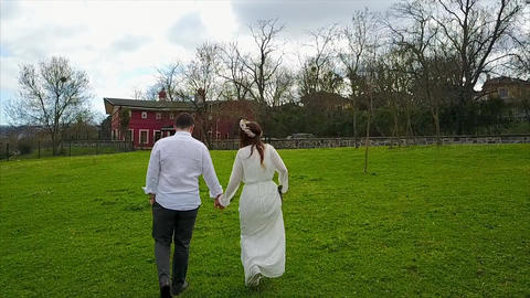 A young couple in love happily walking through grass - holding hands - Aerial Footage