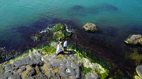 Aerial Of Couple On Cliff next to sea